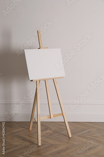 Canvas Print Wooden easel with blank canvas near light wall