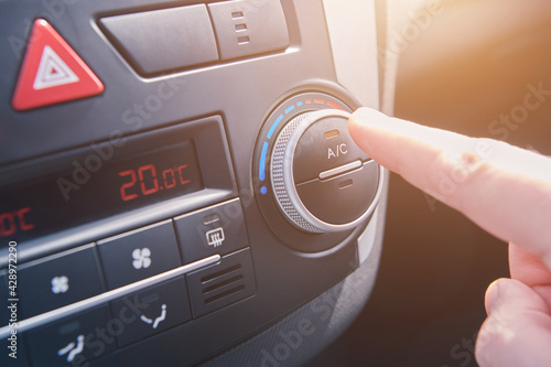 Papel de parede Man hand switches on the air conditioning in the car