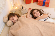 Girls Is Lying On The Floor And Talking Or Sleeping, And Cover Themselves With A Blanket, Home Interior Decorated With Holiday Lights And Gifts