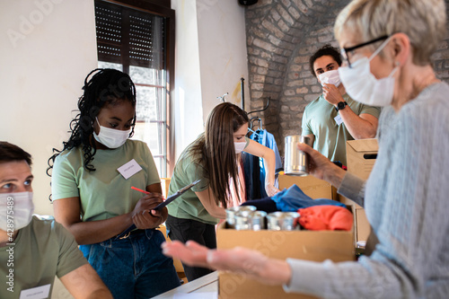 Stampa su Tela Group of volunteers with face mask working in community charity donation center