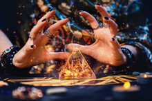 A Witch Conjures A Magic Glass Pyramid. Hands Close-up. Sparks Flare Up Near The Pyramid. The Concept Of Witchcraft And Divination