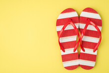 Top View Photo Of Striped Red And White Flip-flops On Isolated Yellow Background With Copyspace