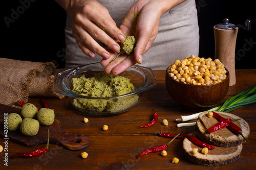Fototapeta Woman with beautiful hands cooking jewish falafel in rustic kitchen on brown wooden board. Healthy vegan food, fitness eating. Falafel indredients. Chickpea in bowl, red chili pepper, green onions obraz