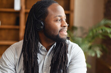 Portrait Of A Cheerful Young Confident African American Male Startup Owner Entrepreneur Standing In The Library Or Office And Looking Away, Close-up Of Intelligent Black Guy With Locks