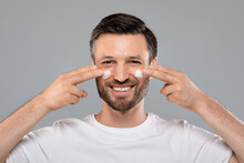 Smiling Handsome Man Applying Cream On His Face, Grey Background