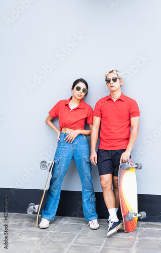 Canvas Print Asian handsome man and cute woman stand on right side, place skateboards in vert