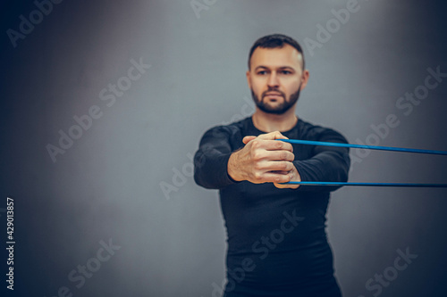 Canvas-taulu Athletic bearded man doing lunge workout exercise with resitance band in gym on grey background