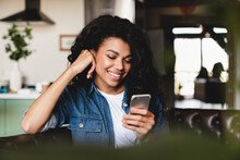 Cheerful African Teenage Girl Using Smart Phone Sitting On The Sofa.Smiling African American Woman Using Smartphone At Home, Messaging Or Browsing Social Networks While Relaxing On Couch