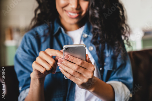 Cropped shot of an african-american young woman using smart phone at home. Smiling african american woman using smartphone at home, messaging or browsing social networks while relaxing on couch - fototapety na wymiar