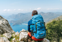 Backpacker Man Sitting On Clifftop And Enjoying The Mediterranean Sea Oludeniz Town Bay During Lycian Way Trekking Walk. Famous Likya Yolu Turkish Route Near Letoon. Active People Vacation Concept.