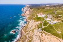 Aerial View Of Cabo Da Roca Lighthouse With Majestic Coastline Looking The Atlantic Ocean, A Famous Landmark In Colares, Lisbon, Portugal.