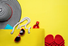 Yellow Beach Bag, Striped Hat And Other Beach Stuff On Yellow Background