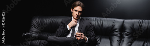 elegant man in suit sitting on leather couch with glass of whiskey on black background, banner. - fototapety na wymiar