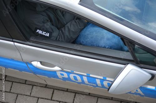 Obraz Policjant przy radiowozie podczas służby w mundurze.  - fototapety do salonu