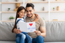 Happy Little Daughter Greeting Young Dad With Card
