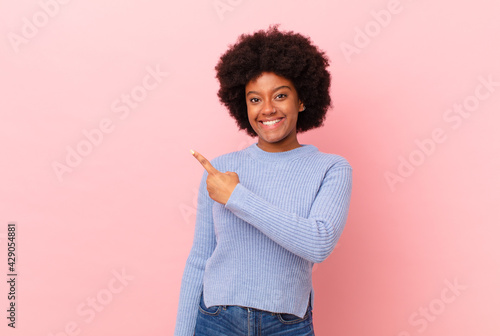 Obraz afro black woman smiling cheerfully, feeling happy and pointing to the side and upwards, showing object in copy space - fototapety do salonu