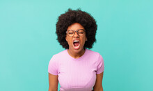 Afro Black Woman Shouting Aggressively, Looking Very Angry, Frustrated, Outraged Or Annoyed, Screaming No