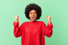 Afro Black Woman Shouting Aggressively With An Angry Expression Or With Fists Clenched Celebrating Success