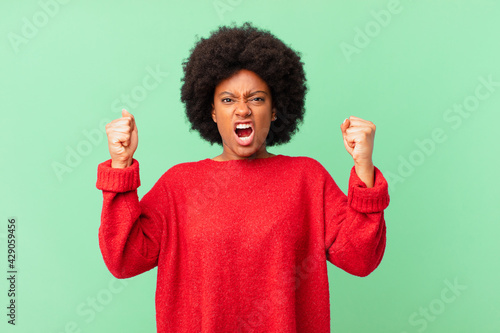 Vászonkép afro black woman shouting aggressively with an angry expression or with fists cl