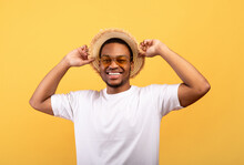 Portrait Of Handsome African American Man In Casual Clothes, Straw Hat And Sunglasses On Yelow Studio Background