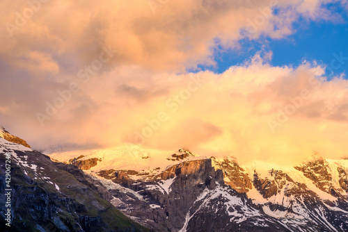 View of beautiful Alps with snow-capped mountain tops and nice clouds at sunset. - fototapety na wymiar