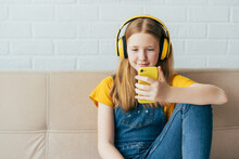 A Beautiful Ginger Teenage Girl Puberty Sits On The Couch At Home And Laughing Looks Into The Mobile Phone And Listens To The Audio In Yellow Headphones. Copy Space. Young Modern People With Gadgets.