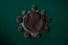 Newborn Dark Green Background - Wooden Bowl With Green Faux Fur, Pine Cones On Dark Background