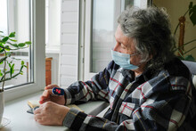An Elderly Man In A Protective Mask On Self-isolation At Home, Measures The Level Of Oxygen In The Blood Using A Pulse Oximeter. Self-isolation Quarantine Due To The Global Coronavirus Pandemic