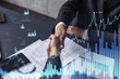 A handshake symbolize a capital market transaction to proceed profit in stock trading. Financial hologram chart over the table with the document. Women in business concept.