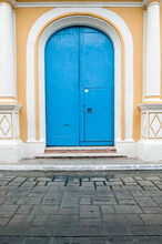 Close Up Of Very Large, Tall Arched Bright Blue Wooden Double Doors With A Smaller Door Cut Into One Set In A  Yellow Spanish Colonial House With Decorative White Columns, Campeche, Mexico