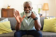 African American Senior Man Sitting On Sofa Making Video Call Smiling And Waving