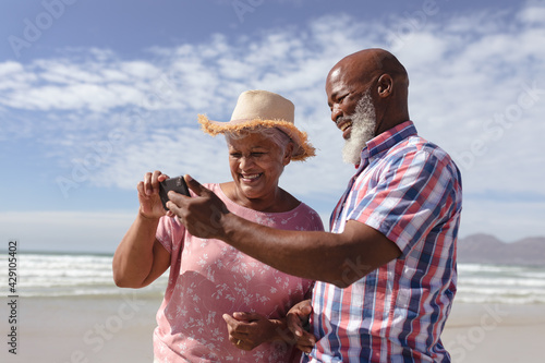 Happy senior african american couple using smartphone at the beach