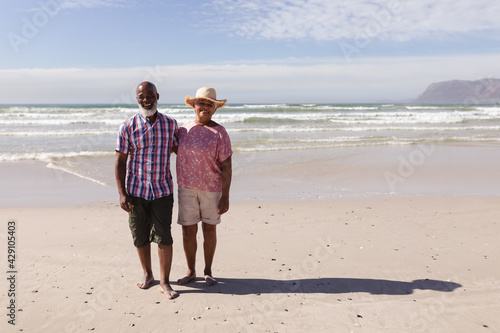 Portrait of happy senior african american couple standing on the beach