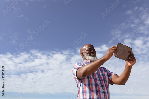 Happy senior african american woman taking a selfie from digital tablet on the beach