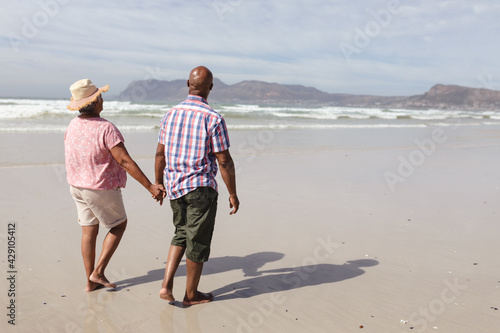 Senior african american couple holding hands walking on the beach