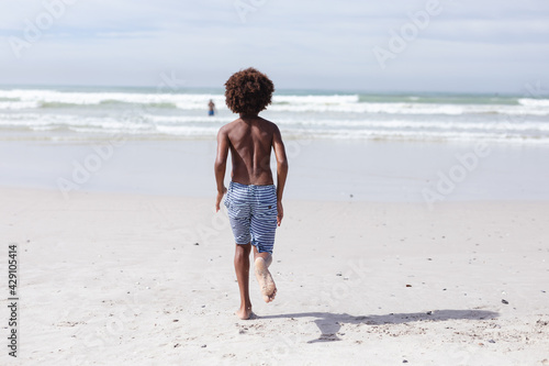 Rear view of african american boy running on the beach