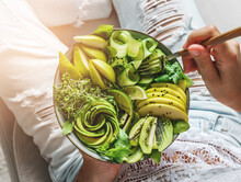 Woman In Jeans Holding Fresh Healthy Greeen Salad With Avocado, Kiwi, Apple, Cucumber, Pear, Greens And Sesame On Light Background. Healthy Food, Clean Eating, Buddha Bowl Salad, Top View, Toning