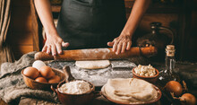 Woman Hands Rolls The Dough With A Rolling Pin On Rustic Wooden Background. Cooking Bread With Cheese, Eggs And Herb. Homemade Healthy Food Concept, Toning