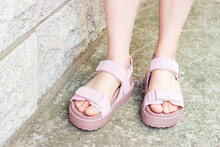 Female Feet In Pink Sandals On Concrete Background Close-up.