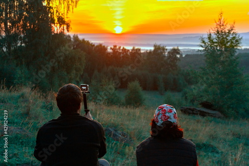Fotografie, Obraz man and woman hikers sit on the mountainside in sun loungers and meet the dawn