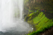 Tourists Walking Behind The Seljalandsfoss Waterfall In Iceland