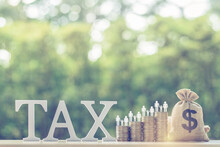 Family Tax Benefit / Residential Property Or Estate Tax Concept : Word Tax, US Dollar Bag, Family Member On Four Rows Of Coin, Depicts Mandatory Financial Charge / Type Of Levy Imposed Upon A Taxpayer