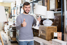 Young Man Satisfied With Purchase Of Stylish Table Lamp In Furniture Store