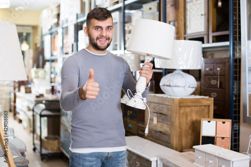Obraz Young man satisfied with purchase of stylish table lamp in furniture store - fototapety do salonu