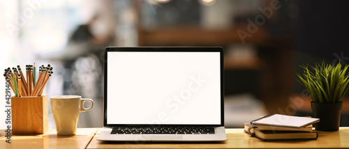 Obraz Front view computer laptop with empty screen, coffee cup, pencil holder, notebook and house plant on wooden table. - fototapety do salonu