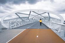 """Back View Of A Male Walking Along De """"Netkous"""" (De """"Groene Verbinding"""") Bridge In Rotterdam"""