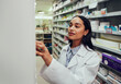 canvas print picture Young woman pharmacist wearing labcoat searching for medicine in shelf in chemist