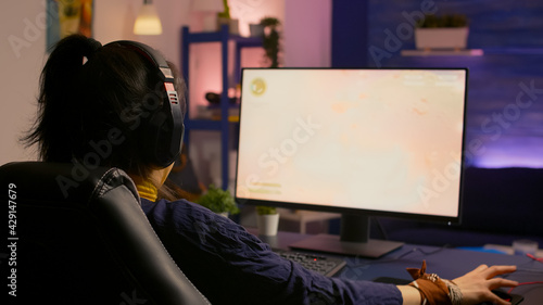 Fotografie, Obraz Concentrated gamer woman losing virtual multiplayer game on powerful computer at home with professional headphones
