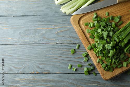 Fresh green onion on cutting board, on gray wooden table Fototapete