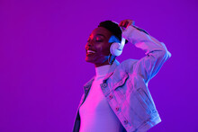 Young African American Woman Wearing Headphones Listening To Music And Dancing In Futuristic Purple Cyberpunk Neon Light Background